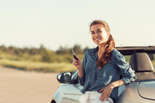 手でキーを持つコンバーチブルの近くに立っている若いきれいな女性 Premium写真