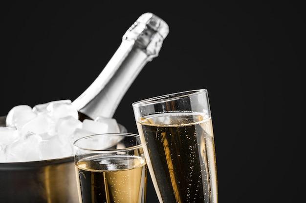 Бокалы с шампанским с бутылкой шампанского в ведре Premium Фотографии