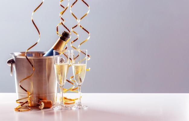 Пара бокал шампанского с бутылкой в металлическом контейнере. празднование нового года Premium Фотографии