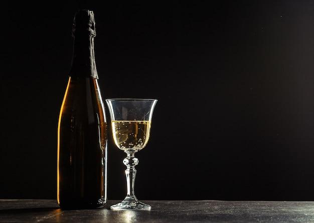 暗闇の中でシャンパンとグラスのボトル Premium写真