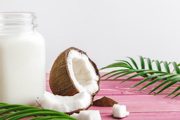 ココナッツとテーブルの上のココナッツミルクのガラス。健康食品 Premium写真