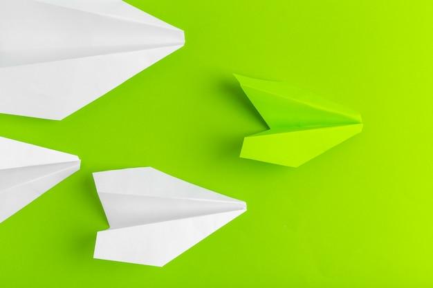 Плоская прокладка бумажного самолетика на зеленом пастельном цвете Premium Фотографии