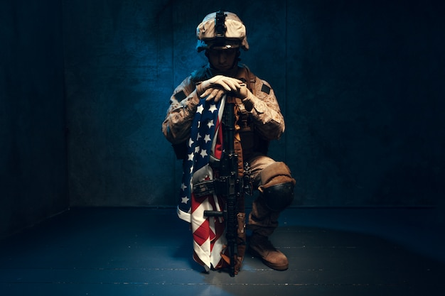 Человек военного снаряжения наемного солдата в наше время с американским флагом в студии Premium Фотографии