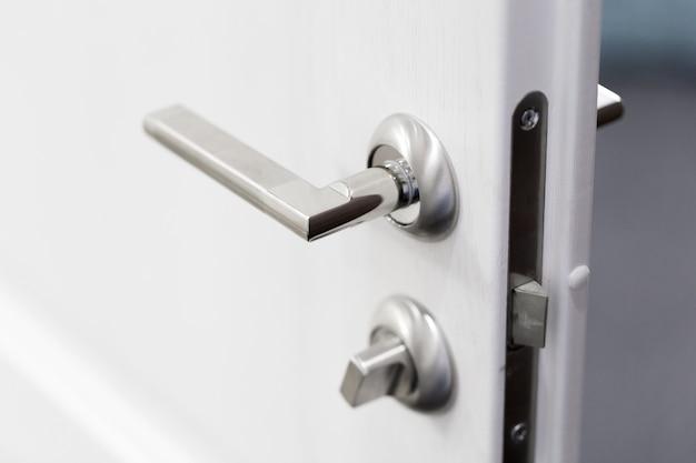 水平の白いドアに金属製のノブの詳細 Premium写真