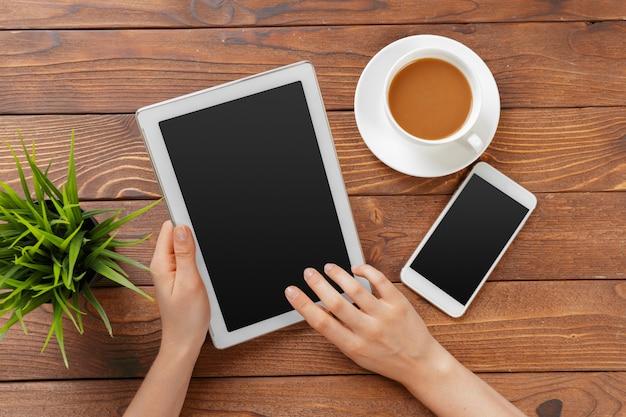 Руки девушки с цифровым планшетом и чашкой кофе на деревянном столе Premium Фотографии