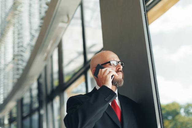 Красивый бизнесмен с помощью смартфона в офисе Premium Фотографии