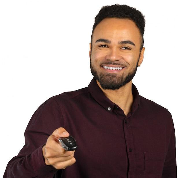 Счастливый черный молодой человек, держащий ключи от машины, изолированные на белом Premium Фотографии