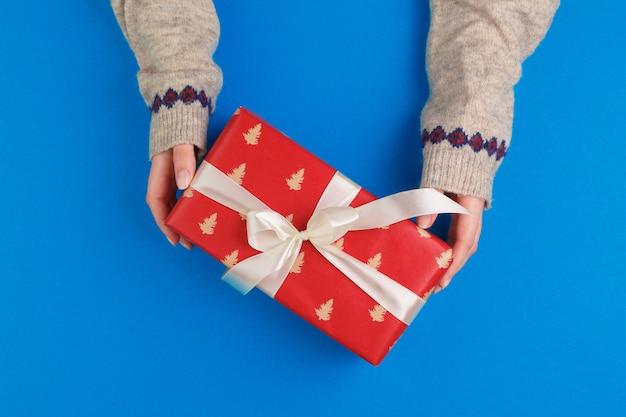Маленькая подарочная коробка в женских руках на синем фоне, вид сверху Premium Фотографии