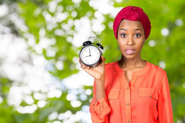 Женщина держит, с тревогой глядя на часы Premium Фотографии
