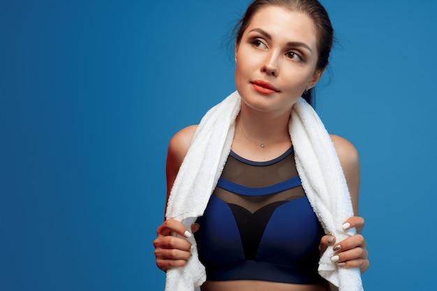 ジムでタオルを保持しているスポーツ服で素敵な若い女性 Premium写真