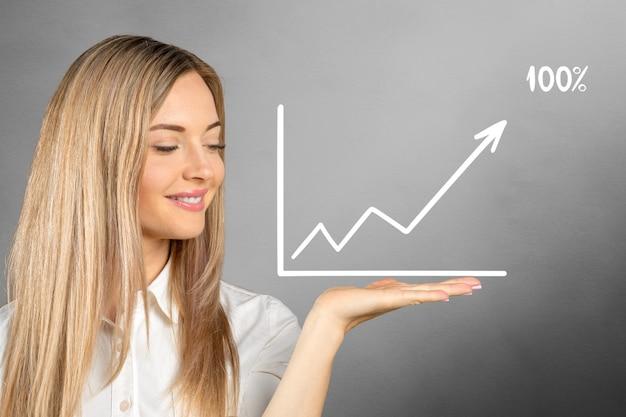 背景に描かれたビジネスグラフを持つ若い女性 Premium写真
