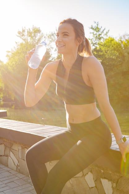 Молодая красивая женщина питьевой воды во время утренней пробежки в парке Premium Фотографии