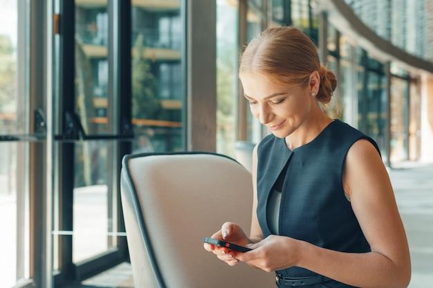 Женщина с помощью мобильного телефона в офисе Premium Фотографии
