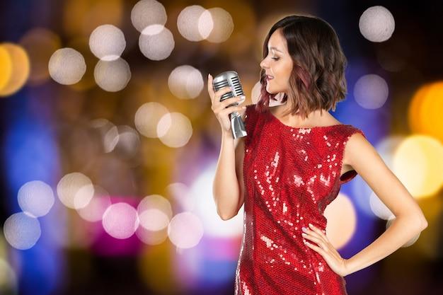 赤い光沢のあるドレスの女性歌手 Premium写真