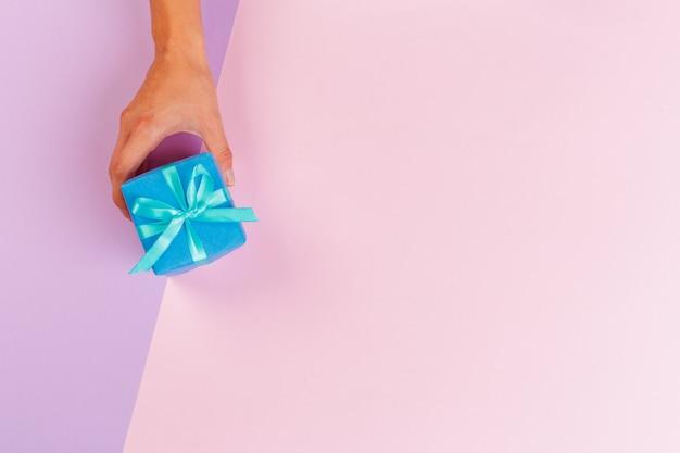 色の背景上のギフトボックスを保持している女性 Premium写真