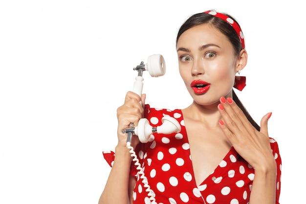 ピンナップスタイルに身を包んだ携帯電話と美しい若い女性の肖像画。 Premium写真