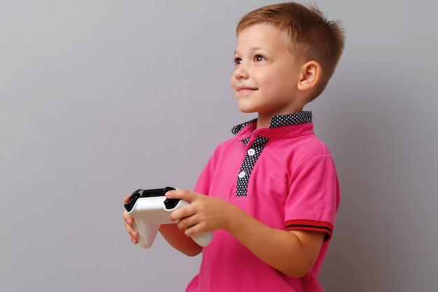 灰色の背景の上のコンソールを遊ぶかわいい男の子 Premium写真