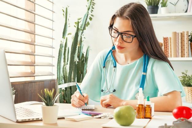 診療所で彼女のテーブルに座っている格好良い女性医師 Premium写真