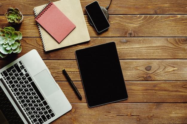 オフィステーブルワークスペーストップビュー。ラップトップ、デバイス、プラント付きの木製デスク Premium写真