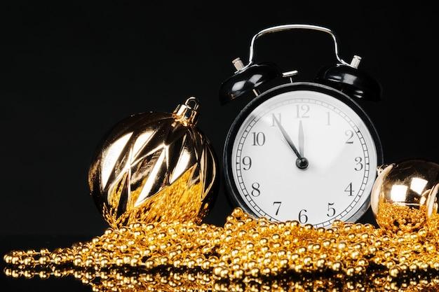 クリスマスつまらないと暗い黒の背景に装飾が施された黒のビンテージ目覚まし時計。クリスマスイブのコンセプト Premium写真