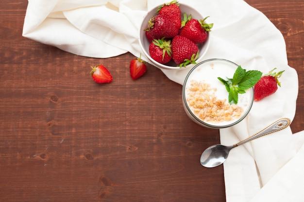 木製のテーブルトップビューで新鮮な果実と健康的なイチゴヨーグルトのガラス Premium写真