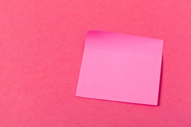 ピンク色の背景に空白の紙片 Premium写真