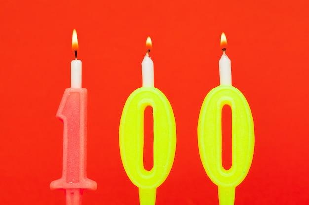 赤の背景にカラフルな燃焼誕生日キャンドル Premium写真