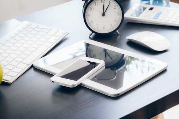 Смартфон и клавиатура компьютера на офисном столе крупным планом Premium Фотографии