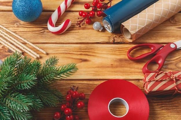 クリスマスのラッピングとコピースペースを持つ木製の背景上のアイテムを飾る Premium写真