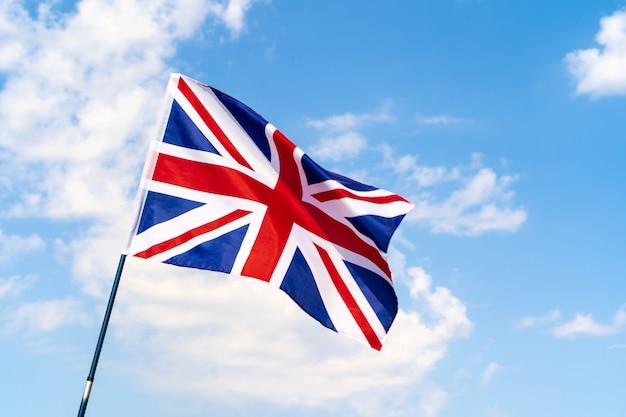 Великобритания флаг развевается на ветру в голубом небе Premium Фотографии