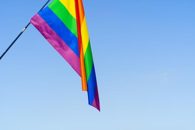 Лгбт развевающийся флаг в небе на флагштоке Premium Фотографии