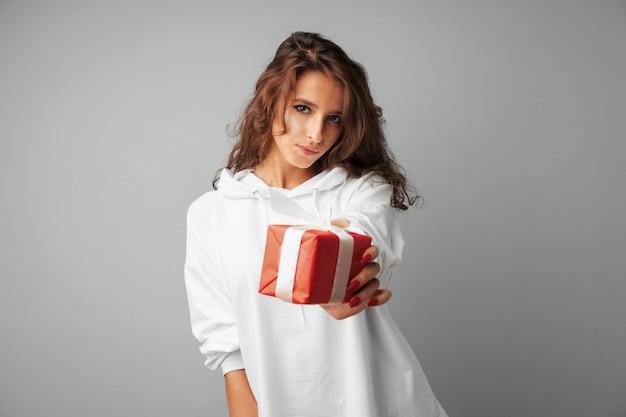 Славная женщина держит в руках красную подарочную коробку Premium Фотографии