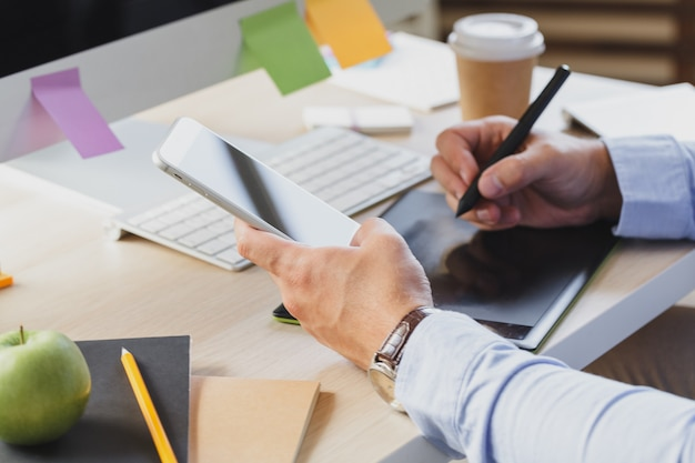 オフィスの机で携帯電話を使用して忙しいビジネスの男の手 Premium写真