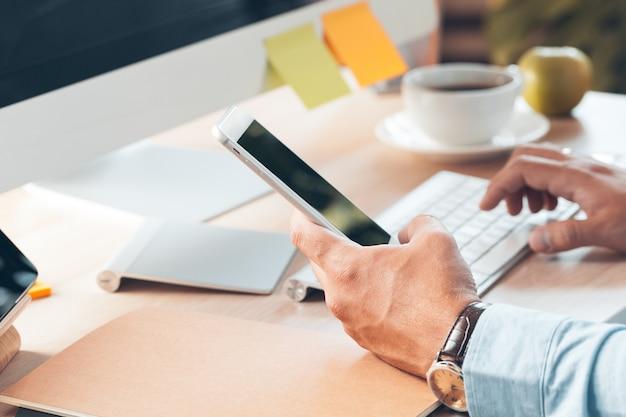 モバイルスマートフォンを使用している人。ビジネスの男性は、オフィスの机で携帯電話を使用して手します。 Premium写真