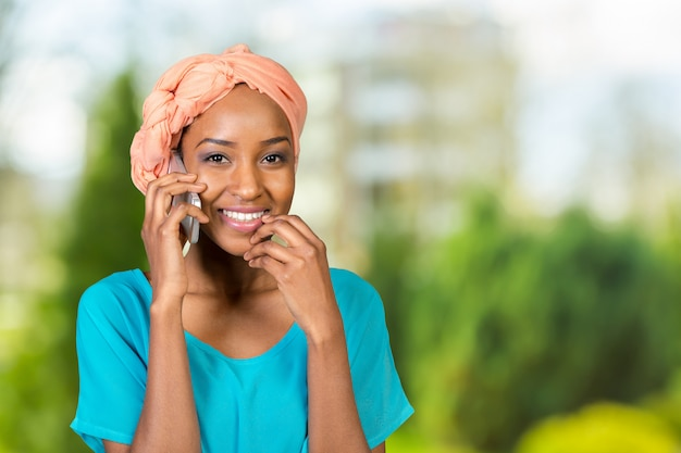 Счастливая молодая негритянка разговаривает по мобильному телефону Premium Фотографии