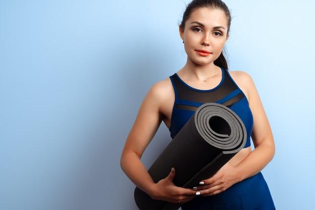 彼女の手でヨガフィットネスマットを保持している若いスリムな女性 Premium写真