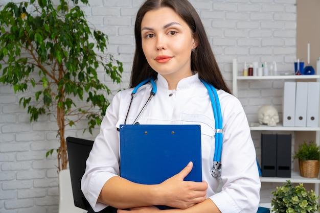 彼女のオフィスでクリップボードで立っている若いブルネットの女性医師 Premium写真