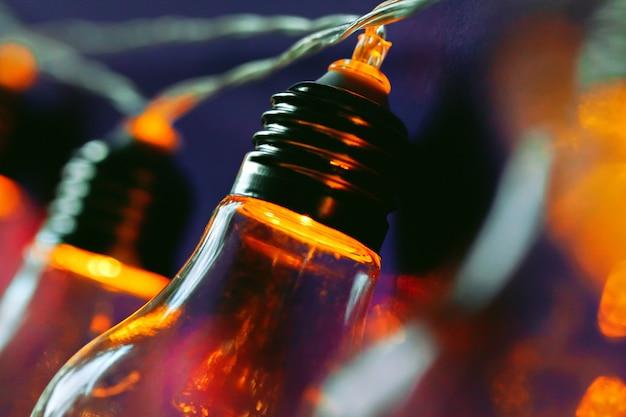 Красивая освещенная праздничная лампочка гирлянды крупным планом Premium Фотографии