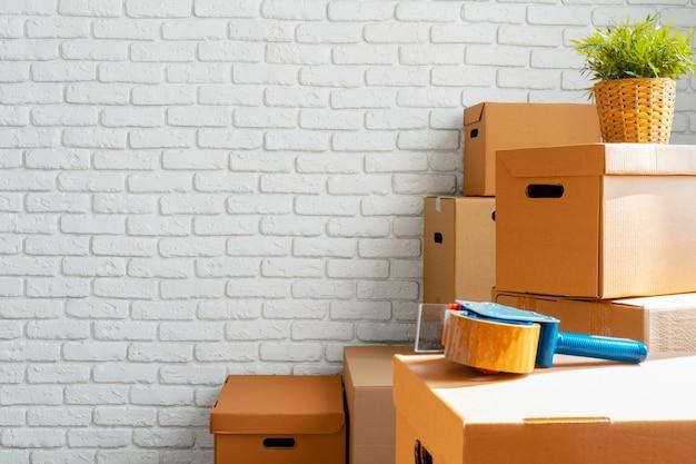Крупным планом движущихся картонных коробок в пустой комнате Premium Фотографии