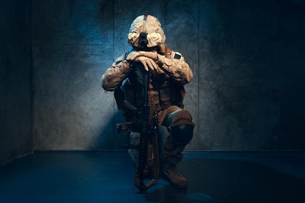 戦争、軍隊、武器のコンセプト。ライフルを保持している民間軍事請負業者 Premium写真