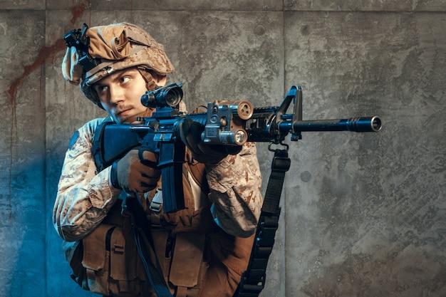 ピストルとアサルトサービスライフルで武装した、迷彩服とヘルメットを身に付けた軍隊兵士 Premium写真