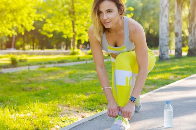 Спортивная женщина в позе бегущего старта в городском парке Premium Фотографии