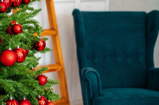 休日のインテリア、美しい装飾が施された青い肘掛け椅子とクリスマスツリー Premium写真