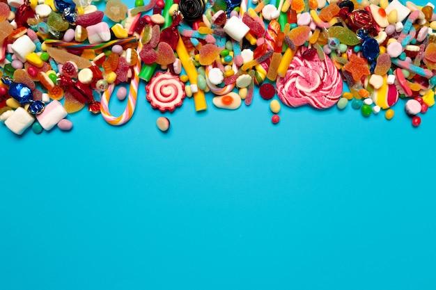 Разноцветные конфеты на синем Premium Фотографии
