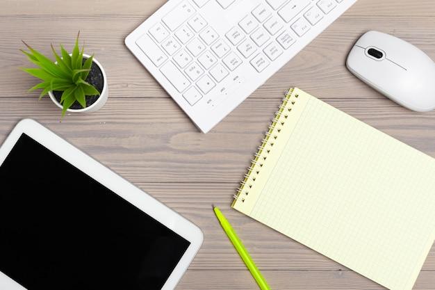 Офисное оборудование, такое как клавиатура компьютера и другие принадлежности на деревянный стол Premium Фотографии