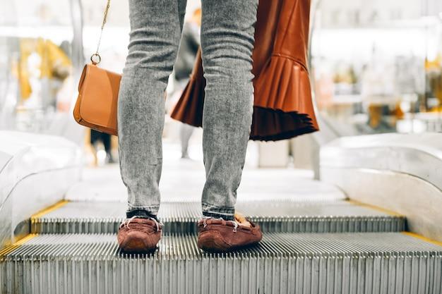 Ноги стоя на эскалаторе в торговом центре Premium Фотографии
