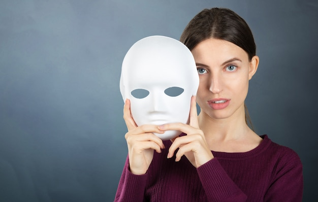 マスクを持つ素敵な女性の肖像画。女性の感情と気分の概念 Premium写真