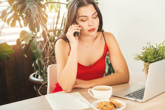 Студентка разговаривает по телефону, сидя в кафе Premium Фотографии