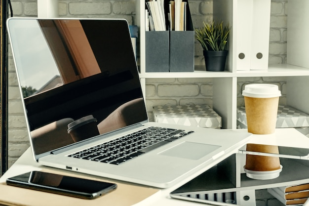 事務用品と作業テーブルの上の明るい部屋でノートパソコン Premium写真