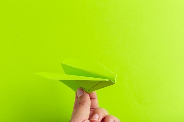人間の手で保持している明るい背景上の紙飛行機。旅行と観光の概念 Premium写真